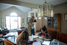 Army Soldier And Wife Hugging While Daughters Do Homework