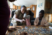 Daughter Sharing Secret With Mother, Assembling Jigsaw Puzzle On Coffe