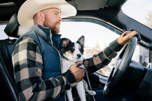 Male Rancher Driving Truck With Dog In Lap
