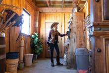 Cowgirl Looking At Equipment O...