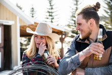 Female Rancher Opening Beer Bottle With Teeth