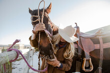 Female Rancher Putting Bridle ...
