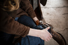 Female Rancher Putting On Cowboy Boot With Spur