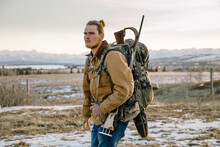 Portrait Male Hunter With Rifle And Backpack On Snowy Ranch