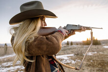 Woman Aiming Rifle In Field During Sunset