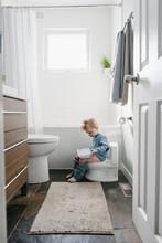 Boy Sitting On Training Toilet...
