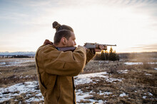 Male Hunter Aiming Rifle In Field At Sunset