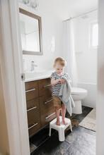 Young Boy Drying Hands In Bathroom