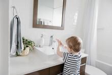 Young Boy Washing Hands In Bat...