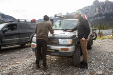 Brothers With Map On Hood Of Overland SUV Below Sunny Mountains