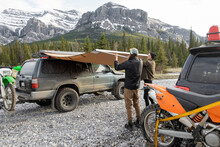 Brothers Preparing Awning For Vehicle Camping Below Mountains, Canada