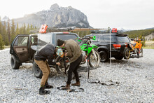 Brothers Fastening Dirt Bike To Overland SUV Below Mountain