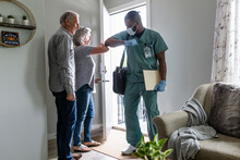 Home Caregiver Greeting Senior Couple With Elbow Bump At Front Door