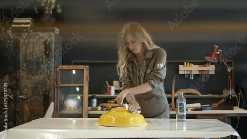 A female restorer painting a yellow detail in workshop, female hands renew old furniture holding a paintbrush Canvas Print
