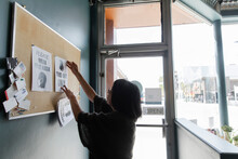 Senior Woman Putting Up Safety Notices In Cafe
