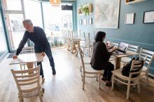 Senior Man Working In Cafe Adj...