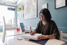 Senior Woman Making Notes In C...