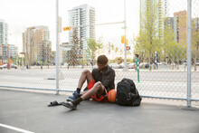 Young Man Putting On Basketball Shoes At Fence Of Urban Court
