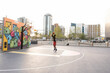 Young man playing basketball on urban court with painted mural