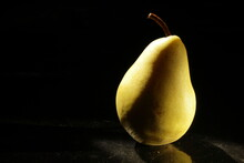 One Yellow Autumn Pear On A Black Background