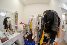 A Room Cluttered With Clothes And A Female Dressing Table With Cosmetics, No Closet