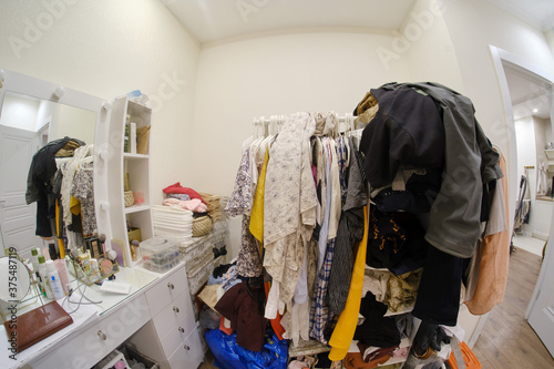 A room cluttered with clothes and a female dressing table with cosmetics, no clo Fototapet