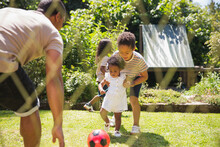 Family Playing Soccer In Sunny...