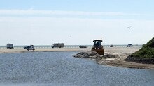 Beach Scene In Port Aransas, Texas With Vehicles Parked And Driving On The Sand, And A Front End Loader Moving Sand Near A Holding Pond. Gulf Of Mexico Is In The Distance.