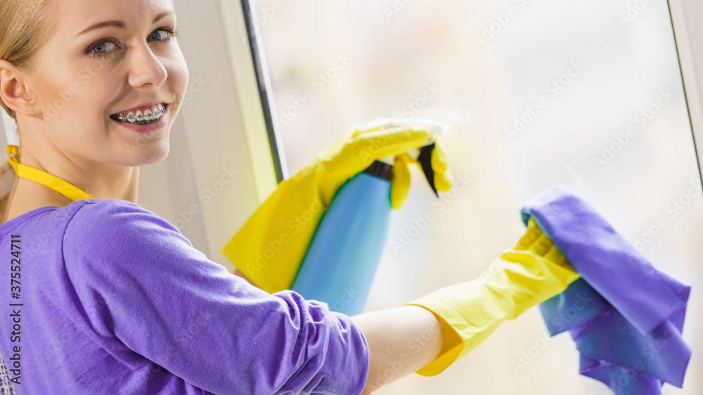 Fototapeta Girl cleaning window at home