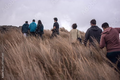 Vászonkép Group of people hiking on sloping filed with long brown grass on a cloudy day