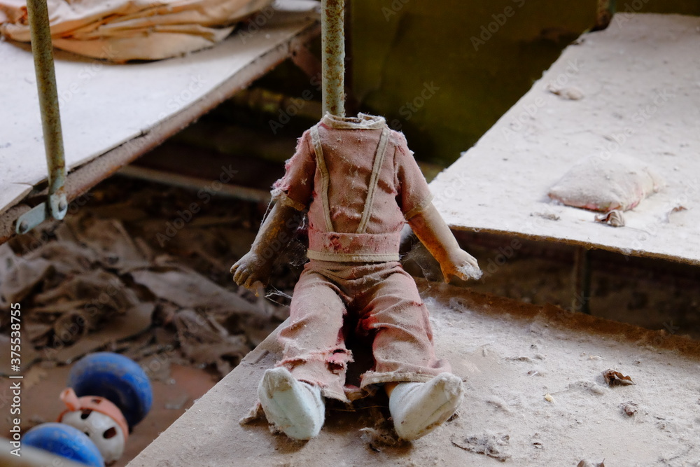 Fototapeta Children's doll without a head. A dirty, broken children's toy from a radiation-contaminated kindergarten in Chernobyl.