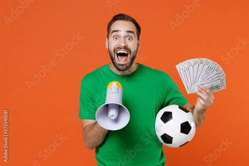 Excited young man football fan in green t-shirt cheer up support favorite team with soccer ball scream in megaphone hold fan of cash money isolated on orange background Canvas