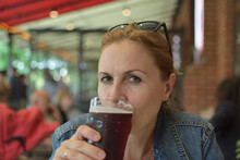 A Woman Drinks A Beer In A Sma...