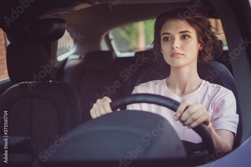 Leinwand Poster Photo of serious taxi driver girl ride drive car traffic town hurry passenger or