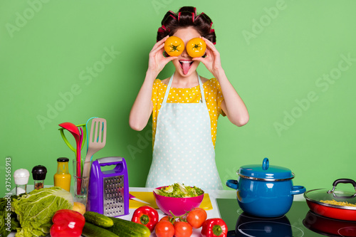 Portrait of her she nice funky crazy naughty housewife cooking vegan salad dish workshop closing eyes with tomato like glasses see showing tongue out fooling isolated green pastel color background