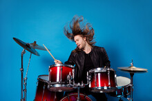 Portrait Of Famous Artist Man Rocker Play Drum Composition On Stage Concert Tour Hold Drumstick Wear Leather Jacket His Hair Air Fly Isolated Over Bright Shine Color Background