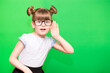 canvas print picture - A young child girl journalist in glasses listening to something holding his hand to ear