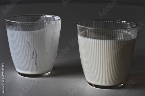 Two glass glasses with kefir, drunk and full Fototapet