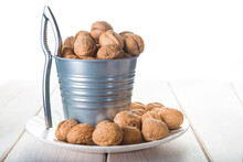 Bucket Full Of Walnuts With A Nutcracker On A White Background