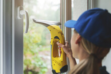 Home Cleaning Service - Worker Washing Window With Vacuum Cleaner