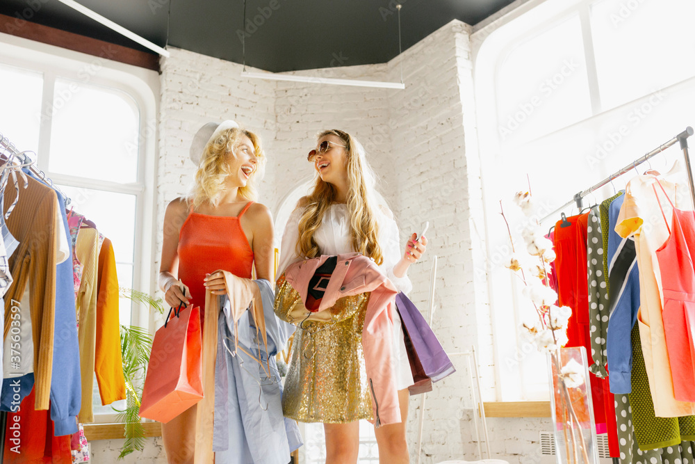 Fototapeta Happy shopping. Wear, clothing shop during sales, summer or autumn collection. Young women looking for new attire. Concept of fashion, style, offers, emotions, sales, purchases. Brand new showroom.