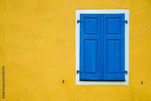 new modern blue closed Shutters, yellow wall of residence house. Canvas