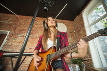 Cheerful. Beautiful Woman In Headphones Recording Music, Singing And Playing Guitar While Sitting In Loft Workplace Or At Home. Concept Of Hobby, Music, Art And Creation. Creating First Single.