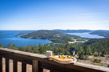 """Skuleberget"" Is Famouse Mountain In Sweden. Amazing Panorama Of The Coast Of ""Hoga Kusten"" And Gulf Of Bothnia. View From The Top. In The Blur In The Foreground Serve The Plate With A Sandwich."