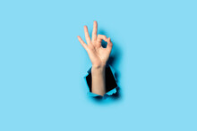 Hand Makes A Gesture Everything Is OK On A Blue Background. Gesture All Is Well, Done