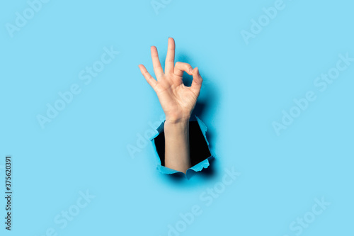 Fotografering Hand makes a gesture everything is OK on a blue background
