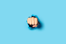 Male Fist Punches A Wall On A Blue Background. Banner. Breakout Gesture, Break