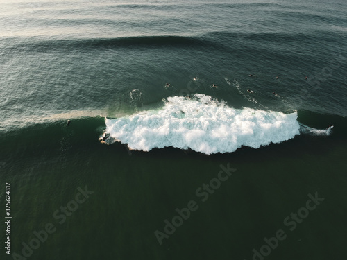 Surfers on a wave from an aerial perspective