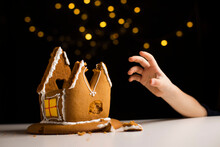 Young Boy Hand Reaching Gingerbread House Leftovers On Table. Delicious Biscuit Dessert Remains
