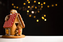 Beautiful Idyllic Gingerbread House With Red Roof Icing, Dark Background With Fairy Lights, Copy Space